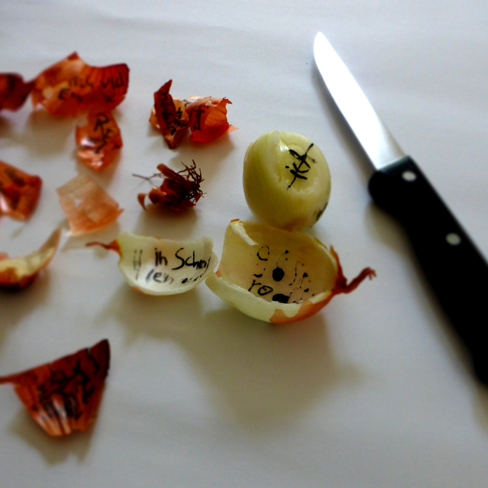 words on onion skins, with kitchen knife. by Ines Seidel